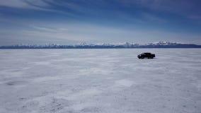 Opinión aérea del abejón del coche en paisaje del invierno y hola velocidad que conduce sobre el lago congelado metrajes