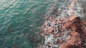 Opinión aérea del abejón de las olas oceánicas que golpean en rocas Opinión del primer del abejón de la costa rocosa con las onda almacen de metraje de vídeo