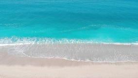 Opinión aérea del abejón de las ondas que se estrellan en una playa arenosa vacía metrajes