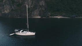 Opinión aérea del abejón de navegar el yate anclada en la bahía con agua del claro y de la turquesa en la puesta del sol Navegand almacen de metraje de vídeo