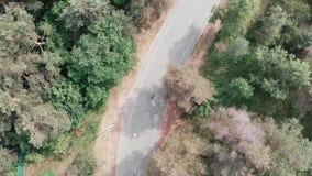 Opini?n a?rea del abej?n la muchacha atractiva joven del triathlete en la ropa de deportes rosada que monta su bici del camino en metrajes
