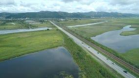 Opinión aérea del abejón del paisaje natural hermoso del camino en prado verde con el río, montañas en fondo almacen de metraje de vídeo