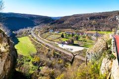 Opinión aérea del campo con el ferrocarril, las montañas, las casas y el campo verde Imágenes de archivo libres de regalías
