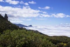 Opinión aérea del paisaje de las nubes que rodean picos de montaña Imagen de archivo libre de regalías