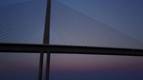 opinión aérea del paisaje marino del abejón 4k sobre puesta del sol caliente asombrosa de la tarde sobre el puente de acero del c metrajes