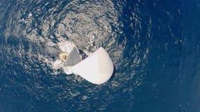 Opinión aérea del paisaje marino sobre un yate blanco del velero en el océano azul debajo del cielo claro almacen de video