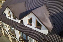 Opinión aérea del primer de los cuartos constructivos del ático exteriores en el tejado de la tabla del metal, las paredes del es foto de archivo