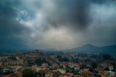 Opinión aérea del pueblo viejo italiano medieval con las nubes y mountai imagen de archivo