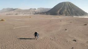 Opinión aérea del tiro cinemático los turistas que caminan en un desierto polvoriento volcánico cerca del soporte hermoso Bromo e almacen de metraje de vídeo