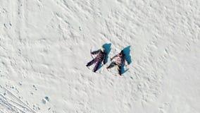 Opinión aérea desde arriba de los niños que mienten en la nieve blanca en sol brillante y que hacen ángeles de la nieve metrajes