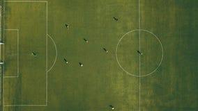 Opinión aérea el equipo de fútbol que practica en el día en campo de fútbol en la visión superior