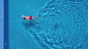 Opinión aérea el hombre en nadadas rojas de los pantalones cortos en la piscina metrajes