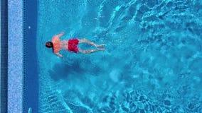 Opinión aérea el hombre en nadadas rojas de los pantalones cortos y y subidas fuera de la piscina almacen de video