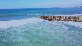 Opinión aérea la costa y personas que practica surf atlánticas en el agua en las ondas en Cascais, Portugal Costa y mar de Clifs metrajes
