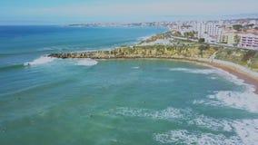 Opinión aérea la costa y personas que practica surf atlánticas en el agua en las ondas en Cascais, Portugal Costa y mar de Clifs almacen de video
