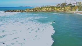 Opinión aérea la costa y personas que practica surf atlánticas en el agua en las ondas en Cascais, Portugal Costa y mar de Clifs almacen de metraje de vídeo