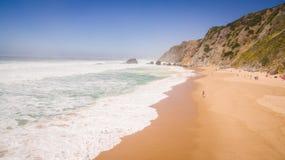 Opinión aérea la gente que descansa sobre la playa de DA Adraga del Praia en Portugal, Almocageme, Sintra Imagen de archivo