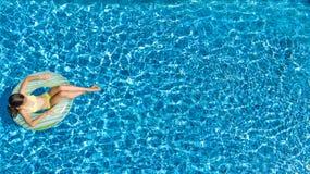 Opinión aérea la muchacha en piscina desde arriba, nadada del niño en el buñuelo inflable del anillo en agua el vacaciones de fam foto de archivo