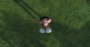 Opinión aérea la mujer que se coloca en la hierba mientras que el abejón está sacando las gafas de sol de su cara metrajes