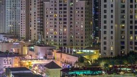 Opinión aérea la playa y los turistas que caminan en JBR con el timelapse de la noche de los rascacielos en Dubai, UAE almacen de metraje de vídeo