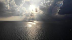 Opinión aérea sobre brillo del sol dramáticamente a través de las nubes y del mar pesados almacen de video