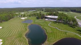 Opinión aérea sobre campo de golf con verde magnífico y la charca almacen de metraje de vídeo