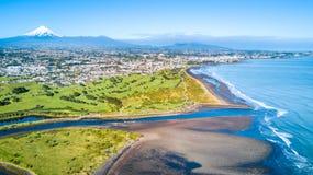 Opinión aérea sobre la costa costa de Taranaki con un pequeño río y nuevo Plymouth en el fondo Región de Taranaki, Nueva Zelanda fotos de archivo