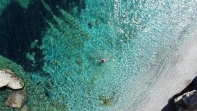 Opinión aérea sobre la mujer que salpica y que da vuelta alrededor en el mar azul almacen de video