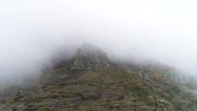 Opinión aérea sobre las montañas rocosas en la niebla tiro Fondo de niebla hermoso de las montañas Pico de montaña en la niebla metrajes