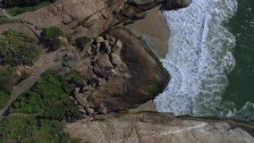 Opinión aérea sobre las ondas y las rocas del mar Fondo hermoso de la naturaleza Colina de Arpoador almacen de metraje de vídeo