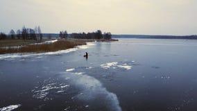 Opinión aérea sobre pescador en un río congelado en Riga, Letonia cantidad 4k metrajes