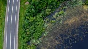 Opinión aérea sobre rápidamente la conducción de los coches en la carretera de asfalto en área del bosque con el lago almacen de metraje de vídeo
