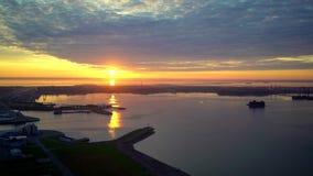 Opinión aérea sobre salida del sol sobre orilla de mar, el agua tranquila, puertos y ciudad almacen de metraje de vídeo