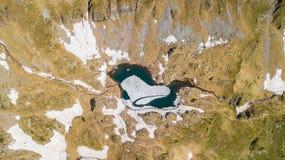Opinión aérea superior y abajo del abejón de un lago natural alpino durante estación de primavera Fusión de la nieve Montañas ita fotos de archivo libres de regalías