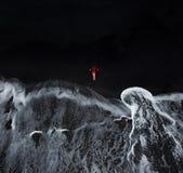 Opinión aérea una muchacha en un vestido rojo que se sienta en la playa con b imagenes de archivo