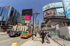 Opinión abajo la calle joven de Toronto de la ciudad con los diversos edificios modernos y la gente que camina en fondo Fotos de archivo