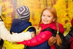 Opinión ascendente cercana de la parte posterior niños con los brazos en hombros Imágenes de archivo libres de regalías