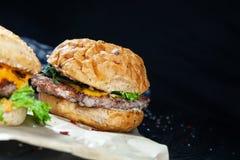 Opinión ascendente cercana sobre la hamburguesa con la carne, la salsa y los verdes en el documento del arte sobre un fondo oscur imagen de archivo libre de regalías