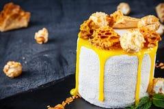 Opinión ascendente cercana sobre la torta blanca sabrosa con la miel, el caramelo y la galleta El postre sirvió en fondo oscuro c fotos de archivo libres de regalías