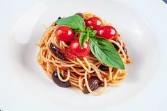 Opinión ascendente cercana sobre las pastas italianas tradicionales con el tomate de la albahaca y de cereza en la placa blanca C imagenes de archivo