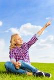 Opinión ascendente cercana sonriente de la muchacha que se sienta en hierba verde Fotos de archivo