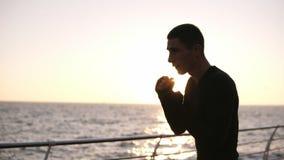 Opinión ascendente cercana un hombre caucásico en vendajes del boxeo en los puños traing al aire libre Luchando con la sombra, sa almacen de video