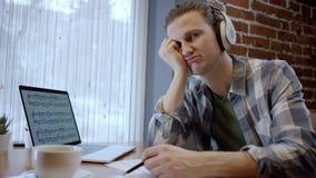 Opinión ascendente cercana un músico joven cansado que intenta componer su nueva canción en un descanso para tomar café duting ab metrajes