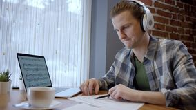 Opinión ascendente cercana un pianista o un guitarrista joven que intenta componer su nueva canción en un descanso para tomar caf almacen de metraje de vídeo