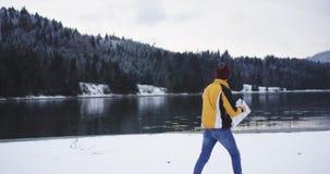 Opinión asombrosa de captura video del paisaje de un lago grande y de un bosque nevoso, turista que da une vuelta al lago de la o almacen de video