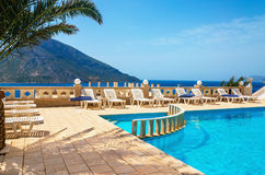 Opinión asombrosa sobre área de la piscina y sunbeds debajo de la palmera w Imagen de archivo