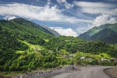Opinión asombrosa sobre el paisaje georgiano con las colinas, el prado, las montañas y el pueblo herbosos verdes el día soleado d imagenes de archivo