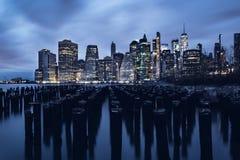 Opinión azul de la hora del Lower Manhattan con los pilones viejos y del East River en el primero plano foto de archivo libre de regalías