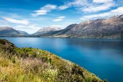 Opinión azul imponente del lago, con el arbusto y las montañas imagen de archivo libre de regalías