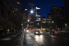 Opinión céntrica de la calle de Toronto con la reflexión de los faros de los coches en el asfalto mojado Fotos de archivo